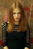 Emotive portrait of a young beautiful red-haired girl wearing tr — Stock Photo