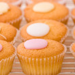 Baked cupcakes with sweet button shaped fondant topping on a cooling rack. — Foto de Stock