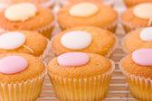Baked cupcakes with sweet button shaped fondant topping on a cooling rack. — Stock Photo