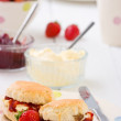 Home-baked scones strawberry jam, clotted cream strawberries, and tea. — Lizenzfreies Foto