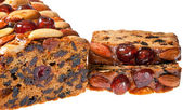 Christmas fruitcake slices with cherries almonds and brazil nuts. — Stock Photo