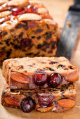 Christmas fruitcake slices with cherries almonds and brazil nuts — Stock Photo