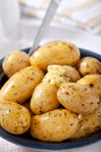 Boild new baby potatoes in a bowl with spoon, herbs, and melting butter. — Stock Photo