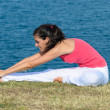 Stretching with sea on the background — Stock Photo