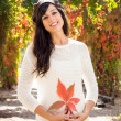 Beautiful brunette with autumn leaf — Stock Photo