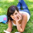 Brunette student with book on grass — Stock Photo #13576218