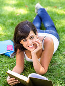 Brunette student with book on grass — Stock Photo