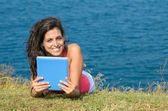 Woman with tablet on vacations in summer — Stock Photo