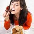 Woman eating crunchy chocolate bar — Stock Photo