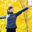 Woman exercising in autumn park — Stock Photo