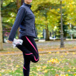 Woman stretching legs and warming up - Stock Photo