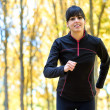 Brunette sport woman running with trees on background — Stockfoto