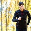 Brunette sport woman running with trees on background — Stock fotografie