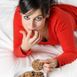Playful woman breaking diet and eating cookie - Stock Photo