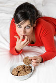 Playful woman breaking diet and eating cookie — Stock Photo
