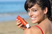 Woman protecting skin with suntan lotion — Foto de Stock