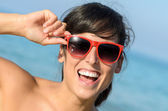 Playful happy woman with red glasses on the beach — Stock Photo