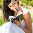 Pretty girl reading and writing in her diary — Stock Photo