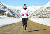 Woman running on winter road — Stock Photo