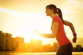 Woman running on summer sunset — Stock Photo