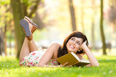 Woman reading book and day dreaming — Stock Photo