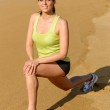 Woman stretching and exercising on beach — Stock Photo