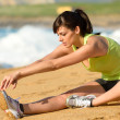 Woman stretching leg on beach — Stockfoto