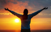 Freedom woman on sunset sky — Stock Photo