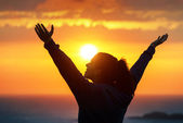 Woman praising and enjoying golden sunset — Stock Photo