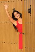 Woman waving at house entrance — Stock Photo