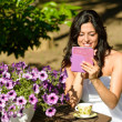 Woman reading ebook in garden — Stock Photo