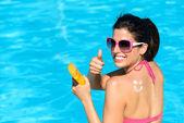 Happy woman applying sunscreen on summer — Stock Photo