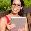 Smart woman reading on table in park — Stock Photo