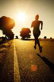 Woman running on sunset — Stock Photo