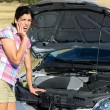 Woman checking broken car engine — Stock Photo