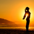 Relaxing exercises on beach at sunset — Stock Photo #35936057