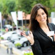 Saleswoman with car keys in trade fair — Stock Photo