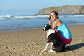 Sporty woman and dog on beach — Stock Photo