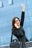 Successful businesswoman on the phone raising arm  — Stock Photo