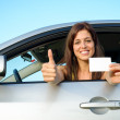 Successful girl in car with driving license — Stock Photo