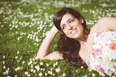 Brunette happy woman relaxing lying on grass — Stock Photo