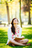 Woman reading book and having fun in park — Stockfoto