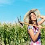 Happy female farmer in corn field — Stock Photo