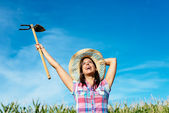 Successful female farmer raising hoe — Stok fotoğraf