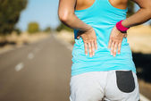 Female runner back pain — Stock Photo