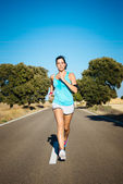 Woman running hard on countryside road — Stock Photo