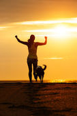 Woman and dog running on beach — Stock Photo