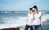 Couple on travel taking photo to beautiful seascape — Stock Photo