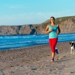 Fitness woman and dog running on beach — Stock Photo #48872471