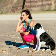 Fitness woman and dog on beach — Stock Photo
